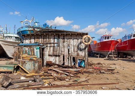 Shabby Small Wooden Building Among Lot Of Board, And Old Rusty Vessels Under Repairing Located On Gr