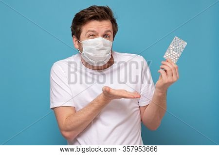 Man In Medical Mask With Pills Has A Sore Throat Pointing On Them Being Unsure.