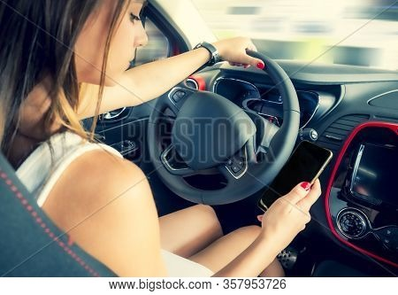 Young Woman Holding Blank Screen Cell Phone While Driving Car. Female Driver Hand On Steering Wheel,