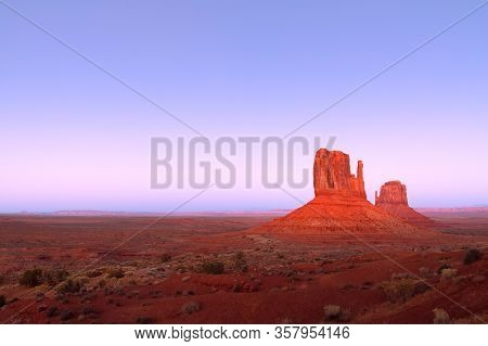 The Last Rays Of The Setting Sun Illuminate Famous Buttes Of Monument Valley On The Border Between A