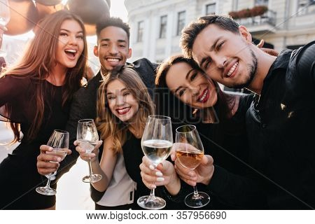 Close-up Portrait Of Laughing Young People Enjoying Summer On The Street And Drinking Champagne. Ent