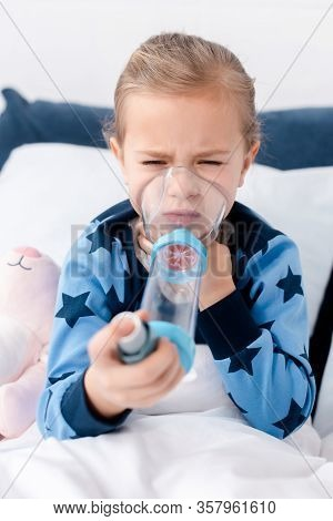 Selective Focus Of Asthmatic Kid Using Inhaler With Spacer