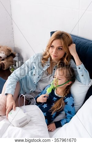 Caring Mother Near Asthmatic Daughter In Respiratory Mask Using Compressor Inhaler