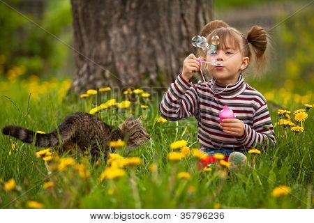 Lovely little girl and a cat, blowing soap bubbles