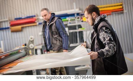 Two Technicians Glue Poster To Foam. Semi Automatic Gluing Machine