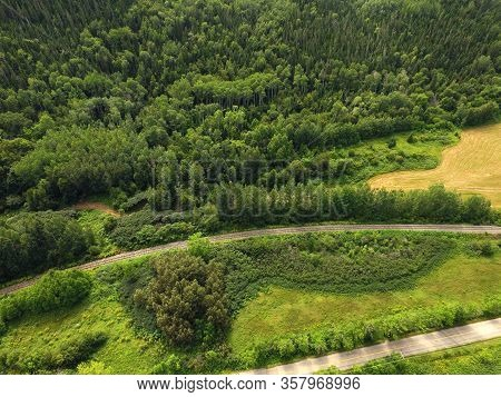 Beautiful Aerial View Of Forested Hill With Train Tracks And Road