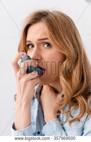 Beautiful And Asthmatic Woman Using Inhaler And Looking At Camera