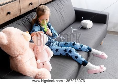 Asthmatic Kid Using Compressor Inhaler Near Soft Toys