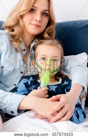 Asthmatic Kid In Respiratory Mask Looking At Camera Near Beautiful Mother