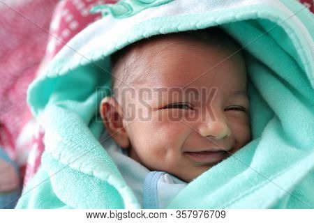 A Smiling Newborn Baby With Dimple In Cheek Wrapped In Sea Green Colored Towel With Hood With Eyes C