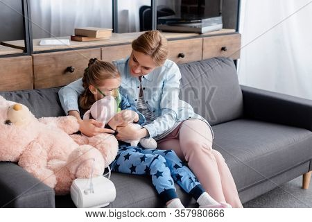 Asthmatic Child Using Compressor Inhaler Near Caring Mother With Soft Toy