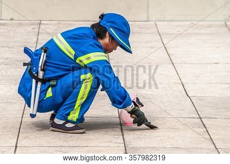 Shanghai, China - May 4, 2010: Worker Street Cleanier In Blue With Yellow Security Lines Removes Gum