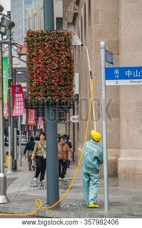 Shanghai, China - May 4, 2010: Male Worker In Green Uniform Waters Hanging Flower Pieces Along Bund,