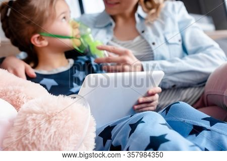 Selective Focus Of Asthmatic Kid Using Respiratory Mask And Digital Tablet Near Mother And Soft Toy