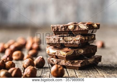 Dark nut chocolate and hazelnuts. Broken chocolate bar on black kitchen table. Pile of chocolate on old wooden table.