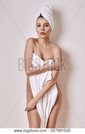 Alluring Young Naked Woman Covering Her Breasts And Front Of Her Torso With A Fresh Clean White A To