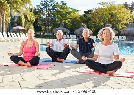 Senior in cross-legged yoga class meditating at the spa pool