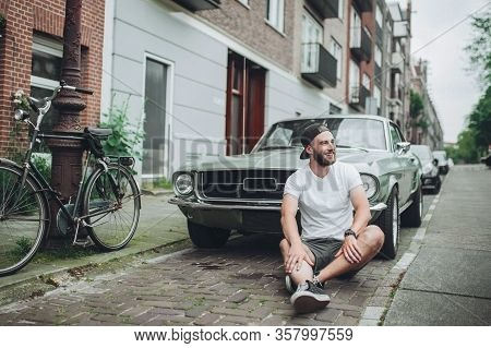 A Guy In A White T-shirt With A Beard Is Sitting On The Sidewalk Near The Old Car