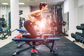 Young Beautiful Brunette Fitness Girl Trains In A Gym On A Sport Equipment. Health Life And Sport Ha