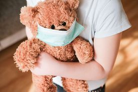 Little Girl Holding Teddy Bear In Medical Mask To Protect From Coronavirus. Stay At Home Concept. Vi