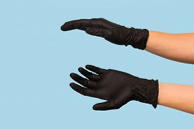 Hand In A Black Medical Glove Holds An Object On A Blue Background. Mock Up, You Can Insert Your Pro