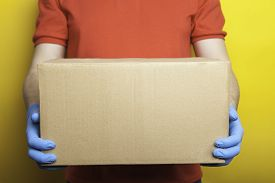 Home Delivery, Online Order. A Man In Uniform, A Medical Mask And Rubber Gloves With A Box, A Parcel