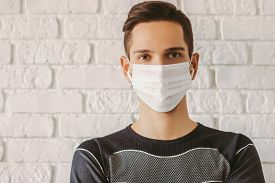Young Sports Man In Protective Mask On Face For Personal Protection Against Covid-19. Training At Ho