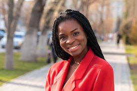 Close Up Portrait Of A Beautiful Young African American Woman With Pigtails In A Red Business Suit S