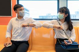 Elbow Bump Is New Novel Greeting To Avoid The Spread Of Coronavirus. Two Asian Business Friends Meet