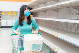 Asian Woman Looking At Supermarket Empty Toilet Paper Shelves Amid Covid-19 Coronavirus Fears, Shopp