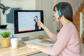 Asian Woman Student Video Conference E-learning With Teacher On Computer In Living Room At Home. E-l