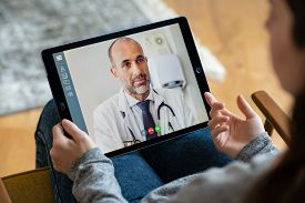 Back view of woman making video call with her doctor while staying at home. Close up of patient in video conferencing with general practitioner on digital tablet. Sick girl in online consultation.