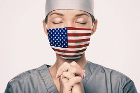 Coronavirus pandemic in the United States of America. USA american flag print on doctor's mask praying with claspeds hands in hope for help. Crying for help, disaster aid needed in the US.