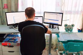 Young Father Working From Home During Quarantine In Children's Room.