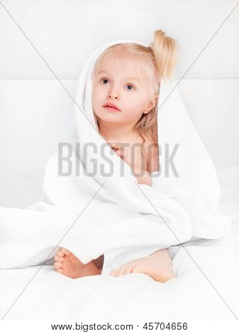 cute two year old girl wrapped into towels after taking a bath