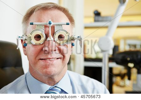 Senior man at optician with trial frame for lens determination