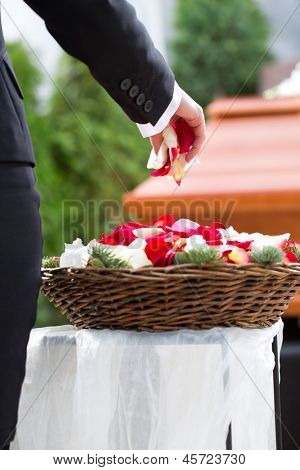 Mourning woman on funeral with flowers standing at casket or coffin