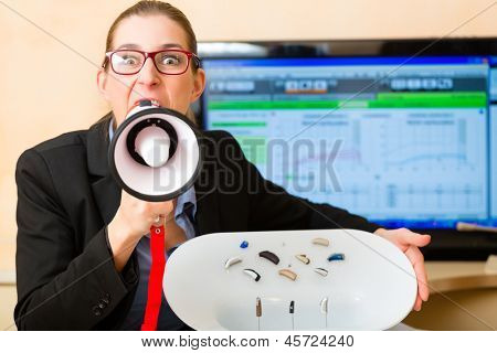 Young Woman or hearing accoustician holding a selection of hearing aids and shout trough a megaphone or loudhailer