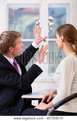 Young lawyer, insurance agent or attorney working in his office and has a consultation with a female customer or a client
