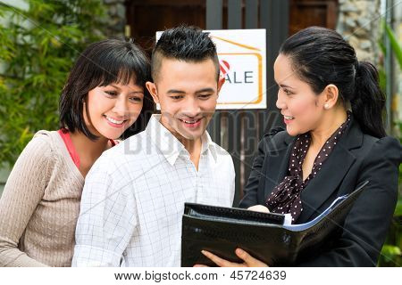 Real estate market - young Indonesian couple looking for real estate apartment or house to rent or buy, the realtor showing a document