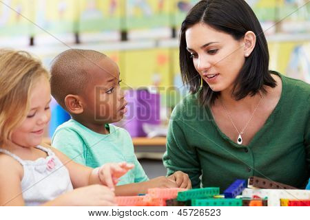 Elementary Pupils Counting With Teacher In Classroom