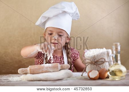 Little girl stretching the cookie dough dispersing some flour over it