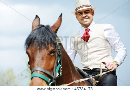 Young stylish man wearing hat riding a horse on countryside with sky and clouds in background poster