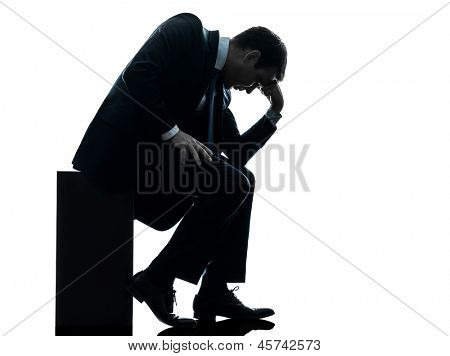 one caucasian sad business man  sitting pensive looking down  in silhouette studio isolated on white background
