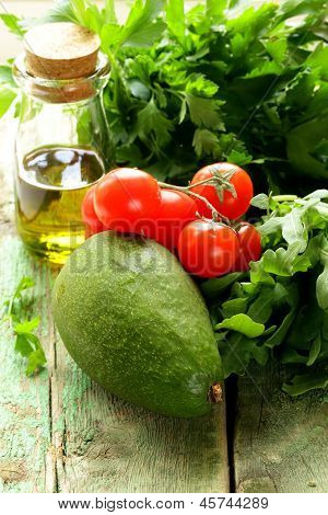 still life of fresh vegetables (avocado, tomato) olive oil and herbs