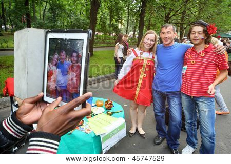 MOSCOW - AUGUST 17: Man is photographed with people in Russian folk costumes at International Festival of Cultures in Sokolniki Park, on August 17, 2012 in Moscow, Russia.