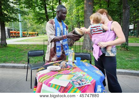 MOSCOW - AUGUST 17: Black man shows drum caucasian baby and her mother at International Festival of Cultures in Sokolniki Park, on August 17, 2012 in Moscow, Russia.