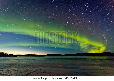 Northern Lights and morning dawn over frozen lake