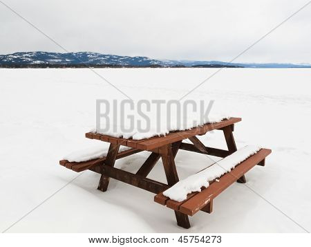 Camp table benches and snowy frozen lake landscape