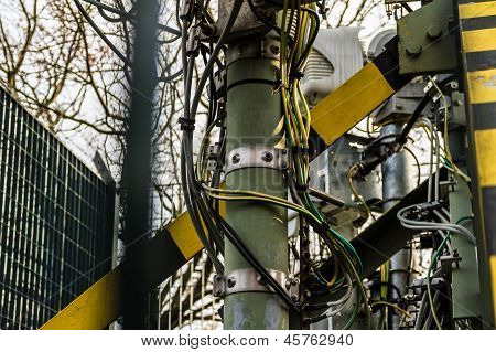 base of a communication tower with various equipment and tangled wires and cables poster